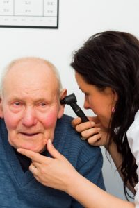 Audiologist examining elderly patient's eardrum with auroscope.